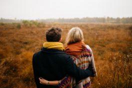 Paar steht auf einem Feld im Herbst