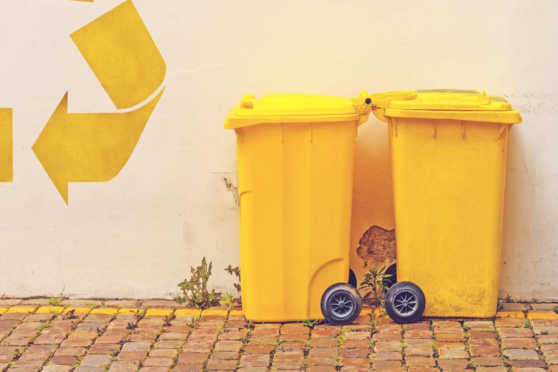Zwei gelbe Mülltonnen auf Kopfsteinpflaster vor einer Wand mit gelben Pfeilen.