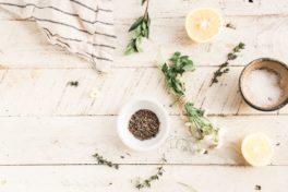 Zwei kleine Schalen mit Kräutern und Salz, zwei Zitronenhälften und Kräuterzweige auf einem Holztisch