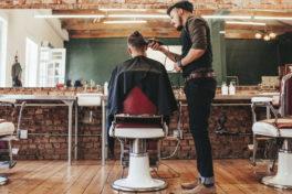 Ein Friseur schneidet einem Mann die Haare in einem Salon.