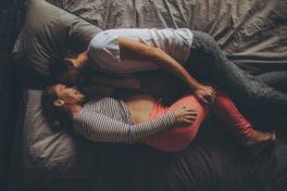 Ein junges Paar liegt auf dem Bett und kuschelt