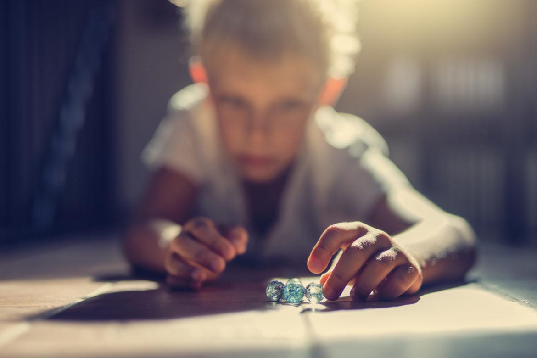 Ein kleiner Junge spielt mit Glasmurmeln