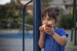 Ein kleines Mädchen isst einen Apfel auf einem Spielplatz