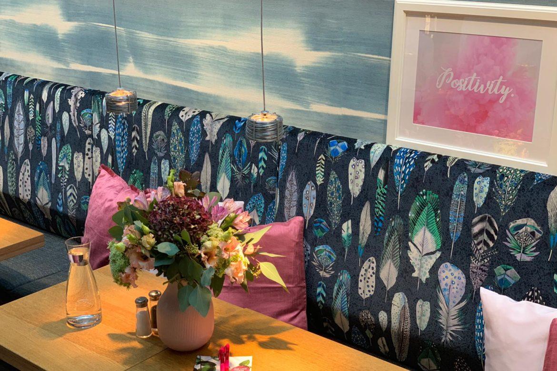 Eine Café-Lounge mit Blumen, Kissen und Bildern.
