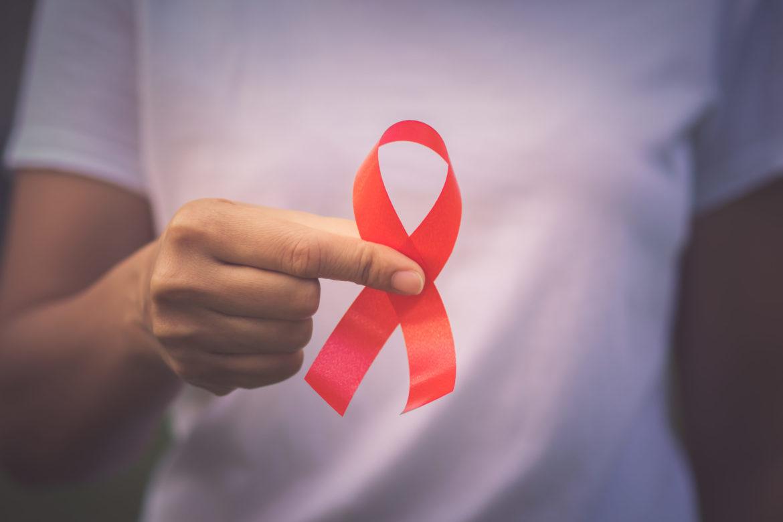 Eine Frau hält eine rote Aids Schleife vor ihrem weissen T-Shirt hoch.