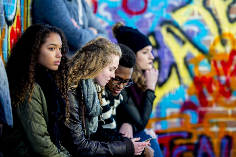Eine Gruppe Jugendlicher sitzt vor einer Graffiti-Mauer und schaut ins Smartphone.