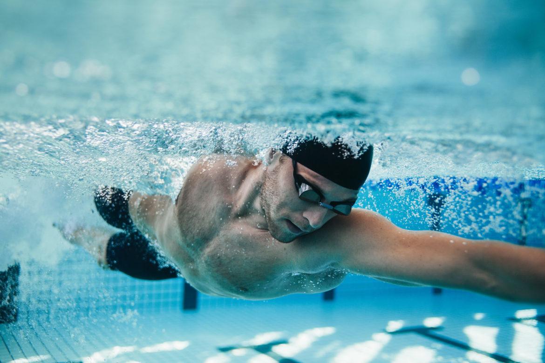 Schwimmer trainiert im Hallenbad und ist unter Wasser zu sehen.