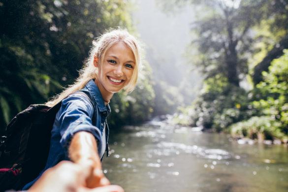 Frau beim Wandern hält die Hand ihres Freundes und blickt zurück