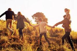 Eine fünfköpfige Familie läuft über eine Wiese und hält sich an den Händen