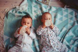 Zwillinge liegen auf einer Ecke und trinken auf einer Nuckelflasche.