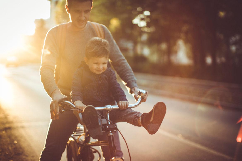 Junger Mann fährt mit kleinem Jungen auf der Stange Fahrrad.