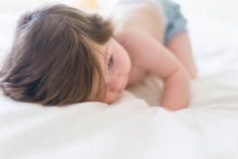 Kleines Kind liegt auf dem Bauch