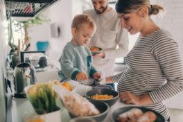 Mann und Frau bereiten Essen mit Kind
