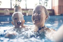 Mutter und Baby beim Schwimmen im Hallenbad