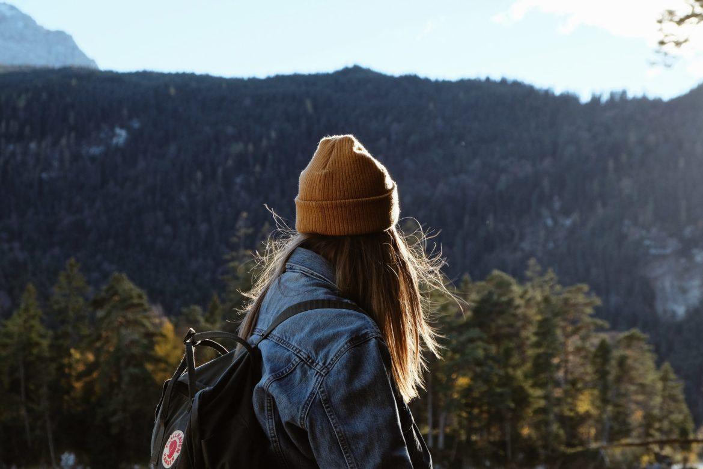Eine Frau mit gelber Mütze und fliegenden Haaren schaut in die Landschaft.