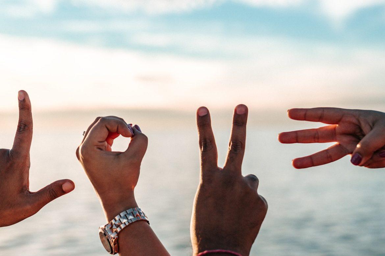 Vier Hände formen das Wort Love