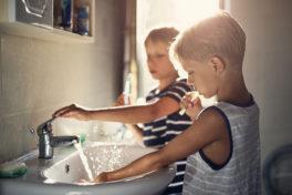 Zwei Jungs putzen sich die Zähne am Waschbecken