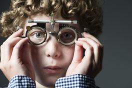 Junge mit Sehtest-Gerät vor den Augen.