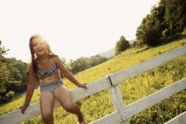 Mädchen sitzt lachend auf einem weissen Zaum im Bikini.