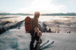 Mann auf Skiern macht Selfi mit Selfiestick vor verschneiter Bergkulisse.