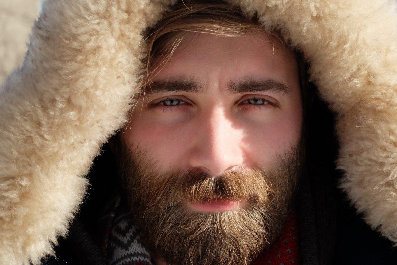 Mann mit Bart und Kunstfellkapuze schaut ins Sonnenlicht.