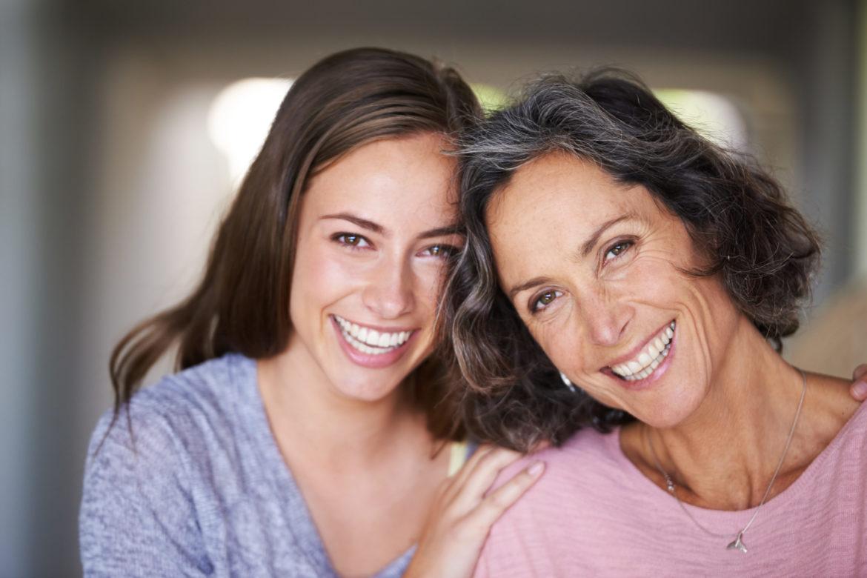 Mutter und Tochter schauen lachend in die Kamera.