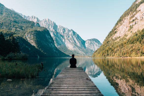 Person auf Steg vor Bergsee
