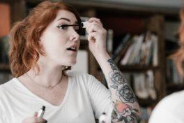 Tattowierte Frau schminkt sich die Wimpern mit Mascara.