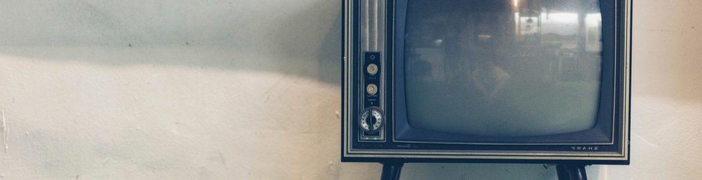 Alter Fernseher auf vier Füssen vor einer weiss-schwarzen Wand