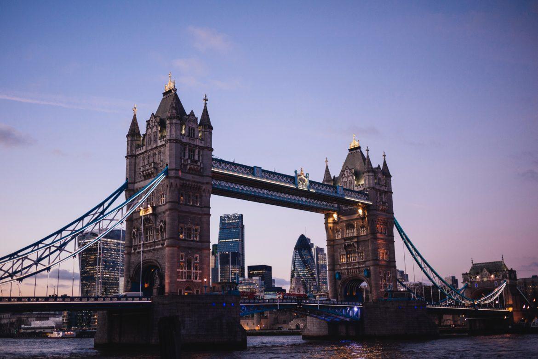 Die Tower-Bridge in London bei untergehender Sonne mit Skyline im Hintergrund.