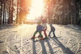 Drei Kinder fahren hintereinander auf einer verschneiten Piste und bei Sonne ski.
