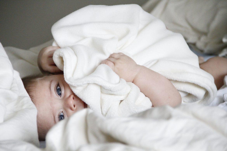 Ein Baby mit grossen blauen Augen liegt im Bett und hält eine weiche, weisse Decke vor sein Gesicht.