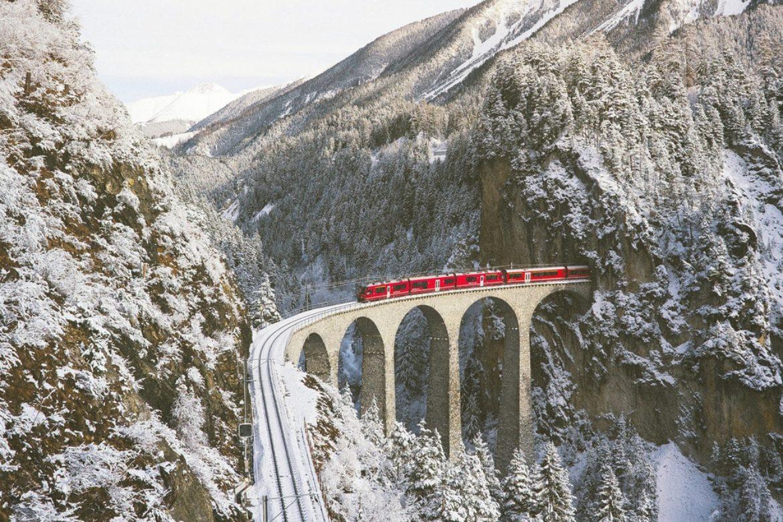 Ein roter Zug fährt auf einem verschneiten Aquädukt durch Wald und Berge.