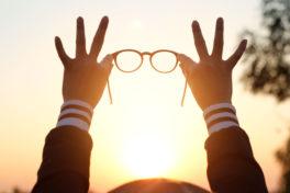 Eine Person die eine Brille in den Himmel mit Sonne streckt.