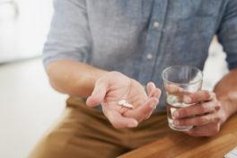 Mann in blauem Hemd und braunen Hosen mit Tabletten und einem Glas Wasser in der Hand.