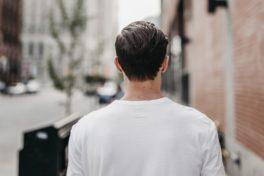 Mann von hinten läuft durch die Stadt.