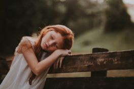 Rothaariges Mädchen sitzt auf Bank mit geschlossenen AUgen und aufgestütztem Kopf.