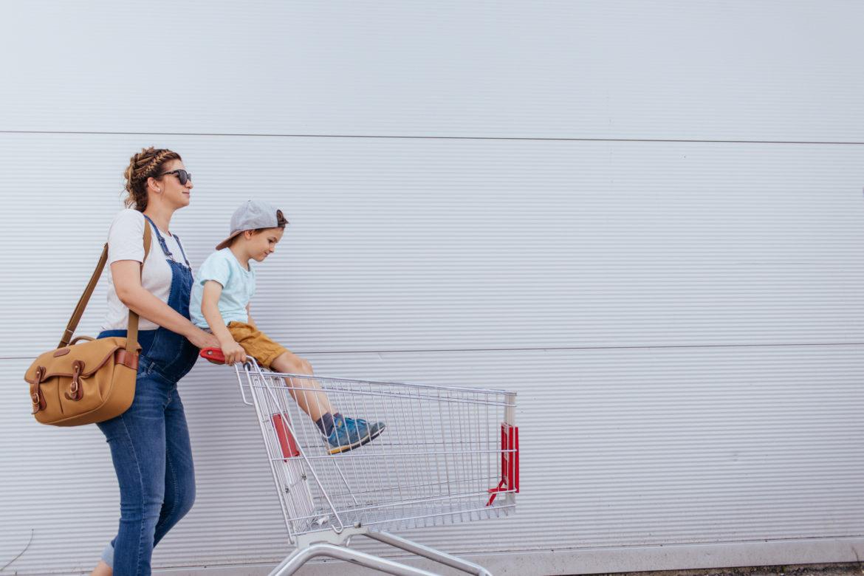 Eine schwangere Frau mit Tasche und Latzhose schiebt einen Einkaufswagen mit einem kleinen Jungen.