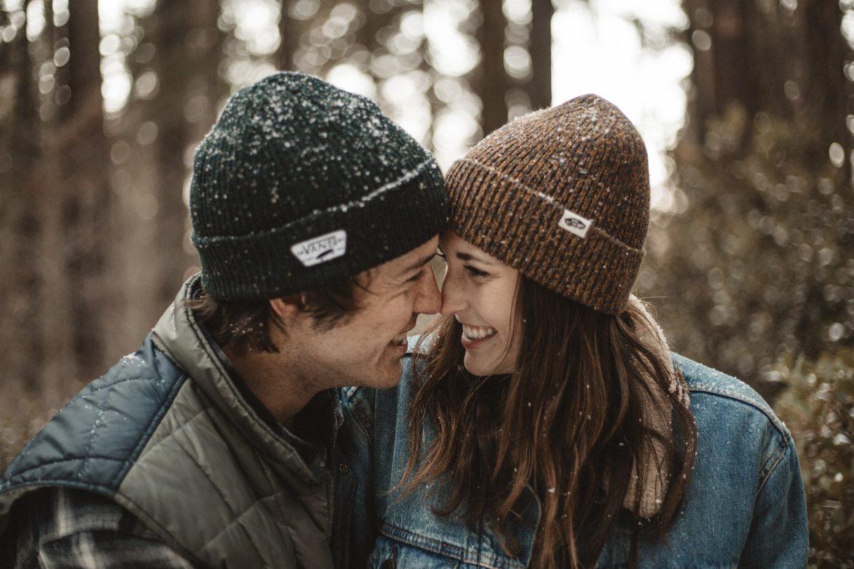 Junger Mann und junge Frau mit Mütze lachen sich Nase an Nase in Umarmung im Schnee an.