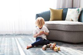 Kind spielt vor Sofa