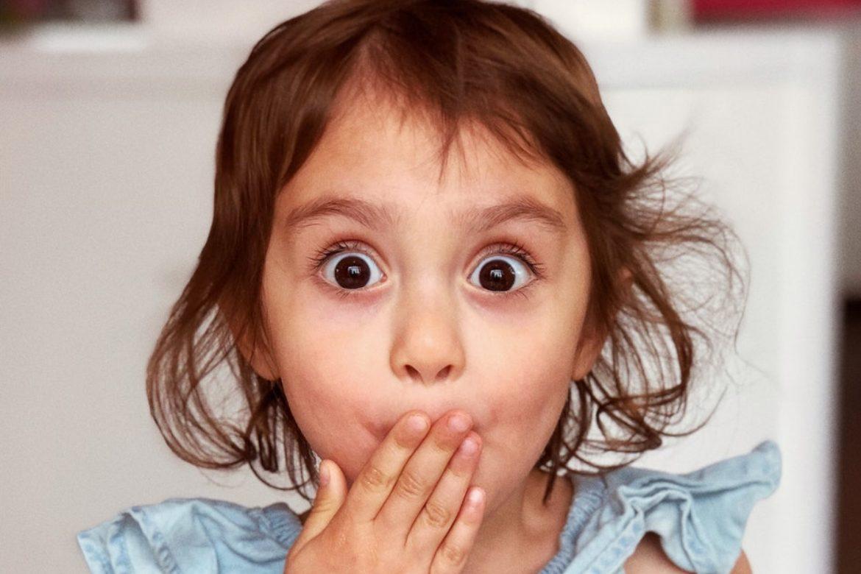 Kleines Mädchen hält sich erschrocken die Hand vor den Mund.