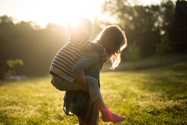 Mädchen trägt jungen auf dem Rücken auf Rasen mit Sonne.