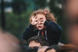 Kind macht Fernglas um die Augen mit eigenen Händen