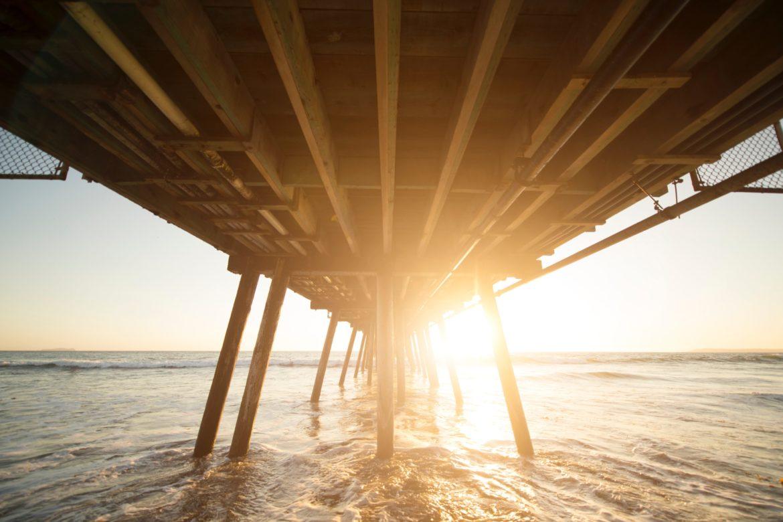 Holzsteg im See mit Sonnenstrahlen
