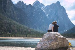 Junges Paar sitzt auf einem Stein und blickt in die Berge