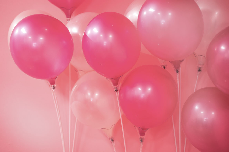 Pink-Metallic Ballons vor rosa Wand.