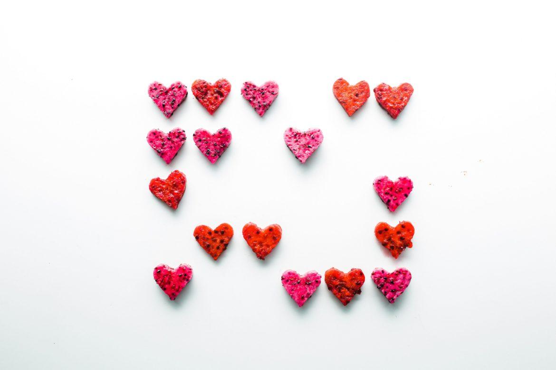 Pinke und rote Kekse in Herzform mit Streuseln.
