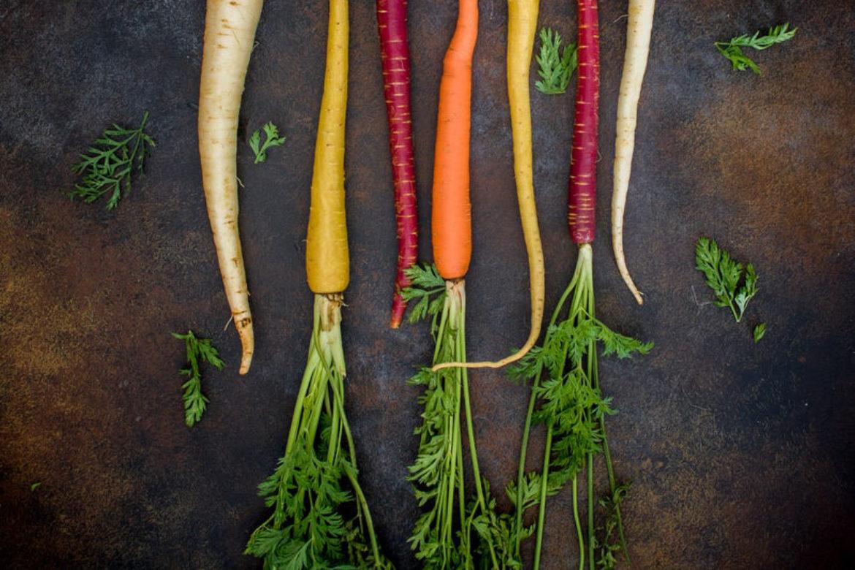 Rote, gelbe, weisse, orange Karotten, Rübli, Möhren auf schwarzem Untergrund.