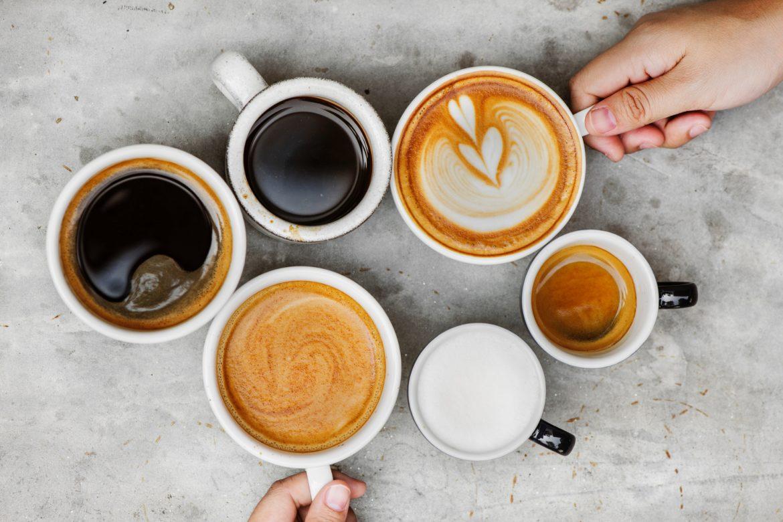 Sechs verschiedene Kaffeetassen auf einem grauen Tisch