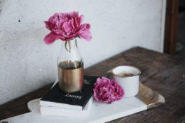 Blume in Vase auf Buch auf einer Kommode mit Tee vor einer weissen Wand